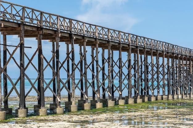 Pilhas de madeira do close-up da ponte de madeira durante a maré baixa. costa da ilha de zanzibar, tanzânia, áfrica oriental