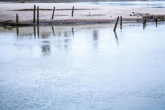 Pilhas de madeira velhas do velho cais arruinado fora da água