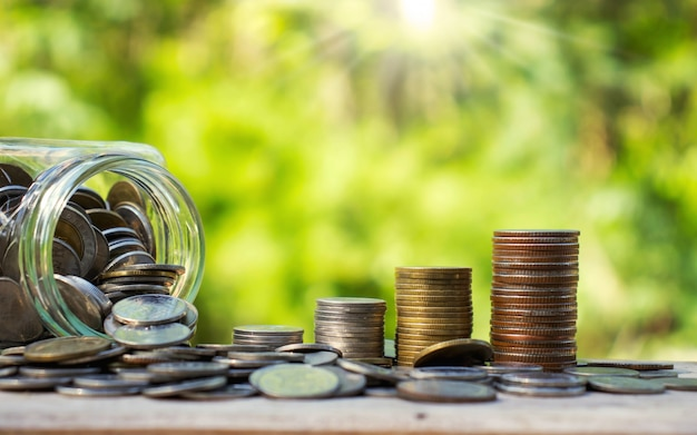 Pilhas de moedas ao lado de garrafas contendo dinheiro na natureza