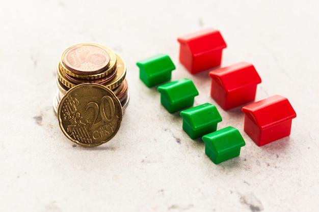 Pilhas de moedas, casa verde e vermelha. hipoteca por casa do dinheiro de moedas
