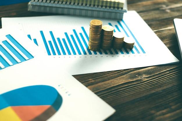 Pilhas de moedas com laptop e gráfico financeiro em papel branco