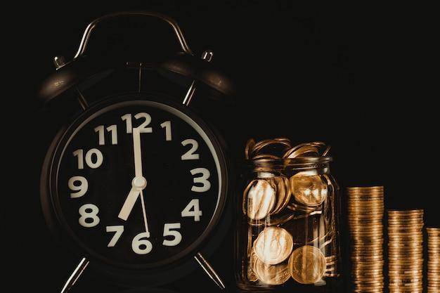 Pilhas de moedas com moeda em frasco de vidro frasco e despertador