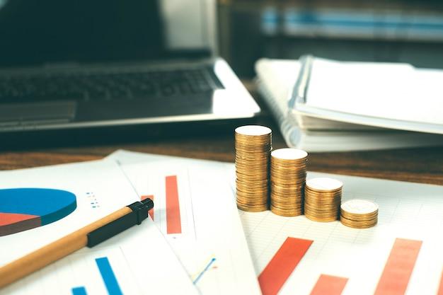 Pilhas de moedas com notebook e gráfico financeiro em papel branco