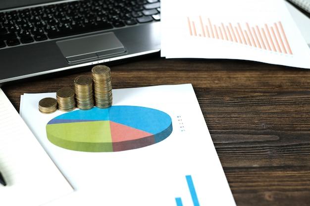 Pilhas de moedas com notebook e gráfico financeiro