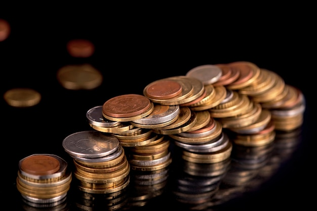 Pilhas de moedas de diferentes países cf em fundo preto.