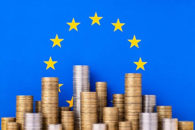 Pilhas de moedas de ouro e prata na bandeira da união europeia