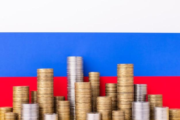 Pilhas de moedas de ouro e prata na bandeira russa