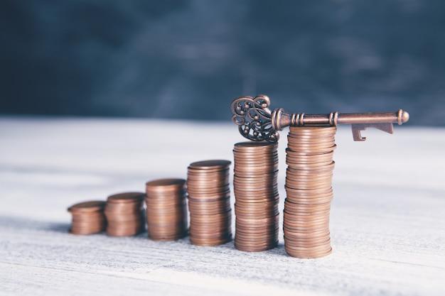 Pilhas de moedas e chaves antigas na mesa de madeira