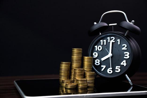 Pilhas de moedas e despertador com computador tablet e gráfico financeiro, visão de planejamento de negócios e conceito de análise de finanças