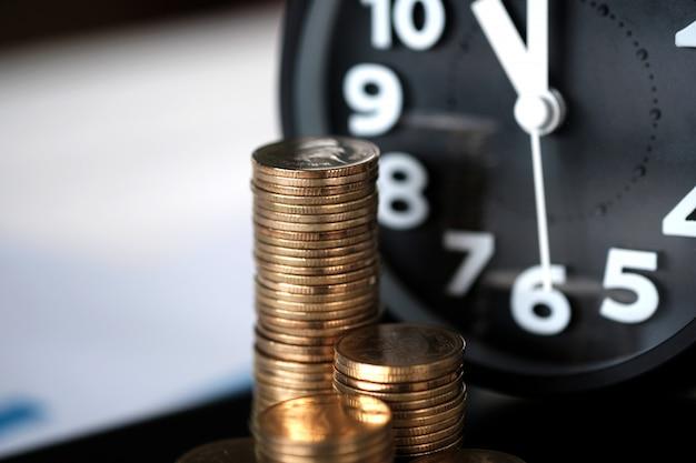 Pilhas de moedas e despertador com computador tablet