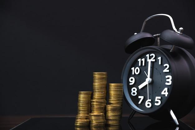 Pilhas de moedas e despertador com mesa