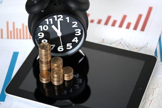 Pilhas de moedas e despertador com tablet e gráfico financeiro