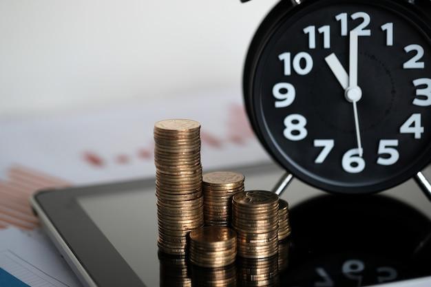 Pilhas de moedas e despertador com tablet e papel gráfico financeiro