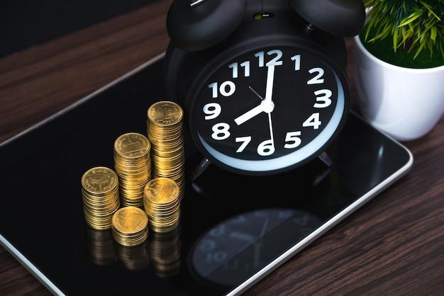 Pilhas de moedas e despertador com tablet