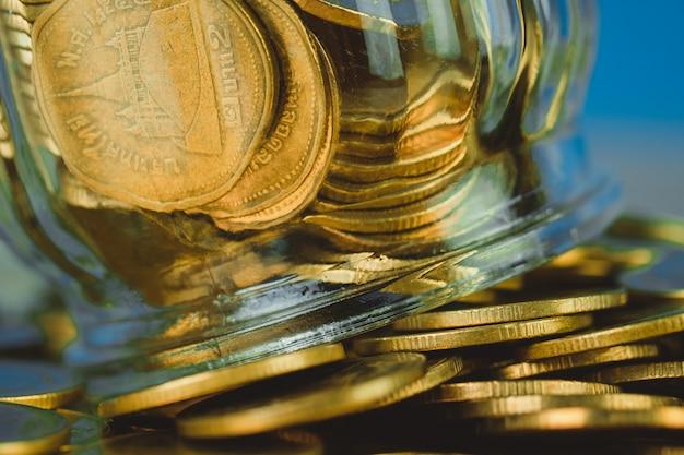 Pilhas de moedas e dinheiro de moeda de ouro no frasco de vidro