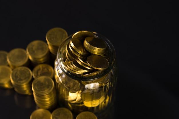 Pilhas de moedas e dinheiro de moeda de ouro no pote de vidro em fundo escuro