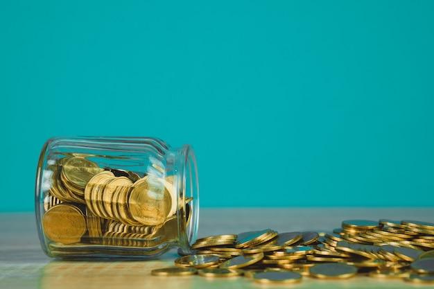Pilhas de moedas e dinheiro de moedas de ouro no pote de vidro na mesa