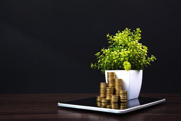 Pilhas de moedas e pequena árvore com tablet
