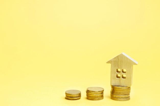 Pilhas de moedas e uma casa de madeira. o conceito de poupar dinheiro para comprar uma casa