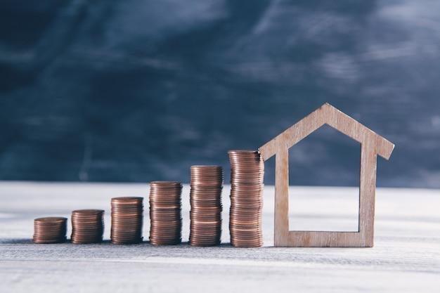 Pilhas de moedas e uma casa modelo antiga