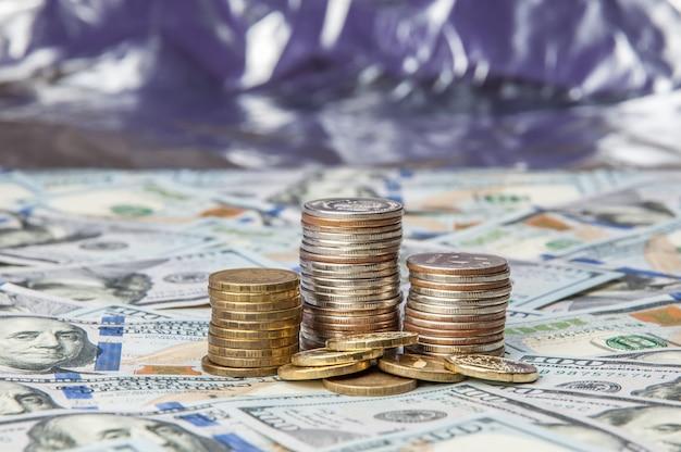 Pilhas de moedas nas notas espalhadas de cem dólares em um fundo brilhante.