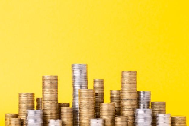 Pilhas de moedas sobre fundo amarelo