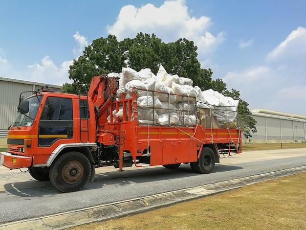 Pilhas de papéis reciclados e sacos de lixo de espuma e plástico no caminhão