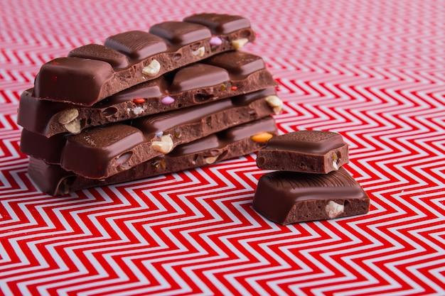 Pilhas de pedaços de barra de chocolate com várias nozes. sobremesa deliciosa e doce.
