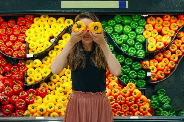 Pilhas de pimentões organizadas no balcão de um supermercado ou mercearia. vende-se pimentões verdes, vermelhos, laranja e amarelos.