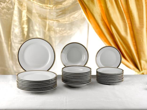 Pilhas de placas de porcelana branca com bordas de ouro de tamanhos diferentes.