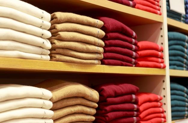 Pilhas de roupas multicoloridas nas prateleiras na loja