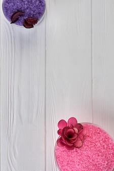 Pilhas de sal de banho rosa e azul na mesa de madeira branca