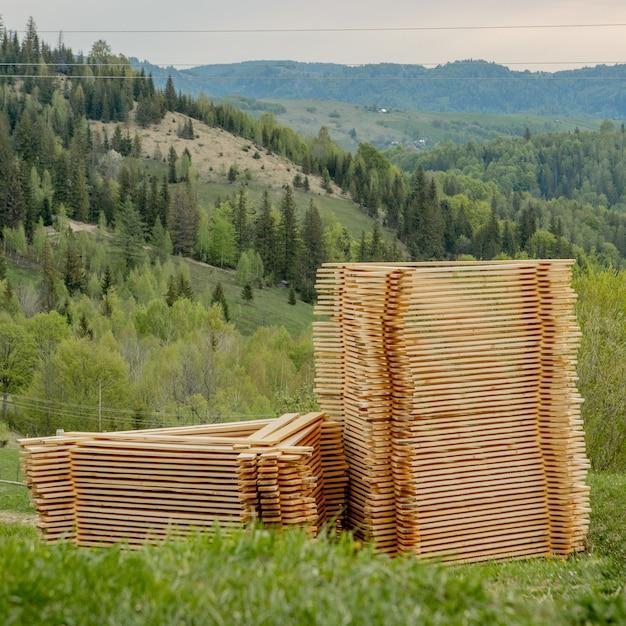 Pilhas de tábuas de madeira na grama verde