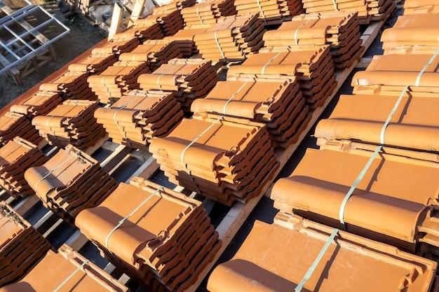 Pilhas de telhas de cerâmica amarela para cobertura de telhados de edifícios residenciais em construção.
