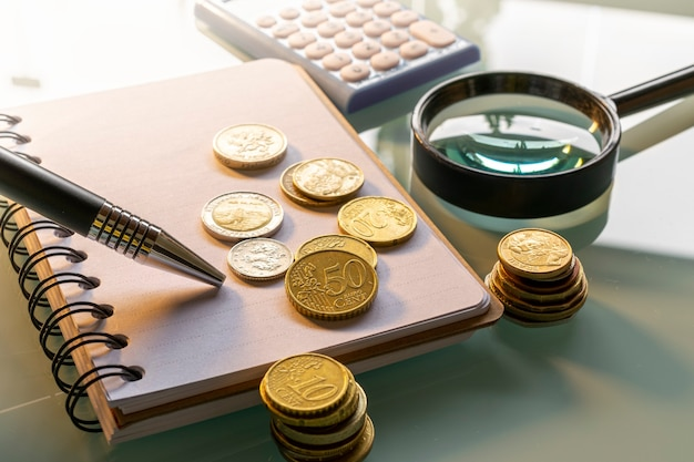 Pilhas de várias moedas com caderno de finanças, lupa, calculadora e caneta.