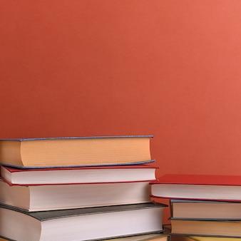 Pilhas de vários livros em um close-up de fundo marrom. de volta à escola, educação, aprendizagem,