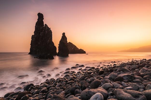 Pilhas do mar durante o pôr do sol na praia da ribeira da janela, ilha da madeira, portugal