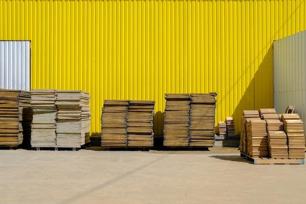 Pilhas lisas de paletes industriais de madeira contra uma parede amarela