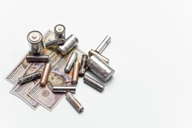 Pilhas usadas velhas e notas de cem dólares