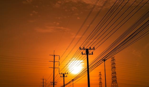 Pilões da eletricidade da silhueta durante o por do sol. poder e energia. conservação de energia.