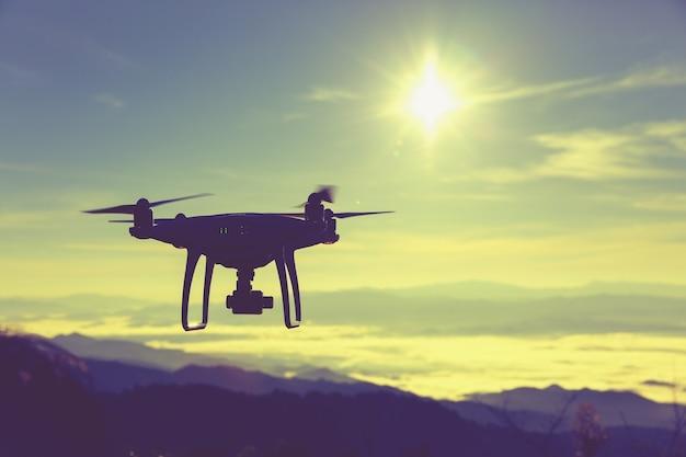 Pilotagem de drone ao nascer do sol sobre o nevoeiro.