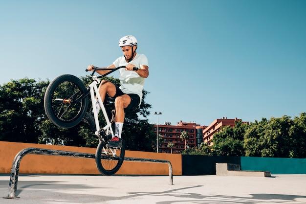 Piloto adolescente do bmx que executa truques no skatepark