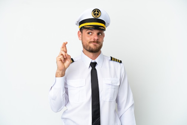 Piloto brasileiro de avião isolado em fundo branco com dedos se cruzando e desejando o melhor