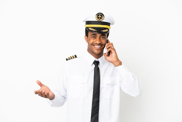 Piloto de avião afro-americano sobre fundo branco isolado, conversando com alguém ao telefone celular