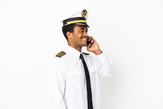 Piloto de avião afro-americano sobre fundo branco isolado, conversando com o telefone celular