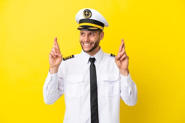 Piloto de avião caucasiano isolado em fundo amarelo com os dedos se cruzando