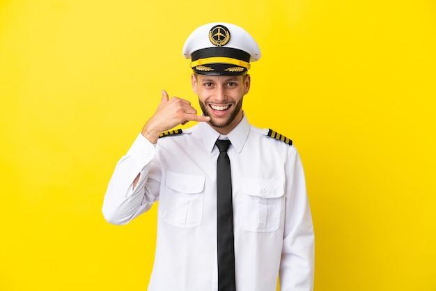 Piloto de avião caucasiano isolado em fundo amarelo, fazendo gesto de telefone. ligue-me de volta sinal