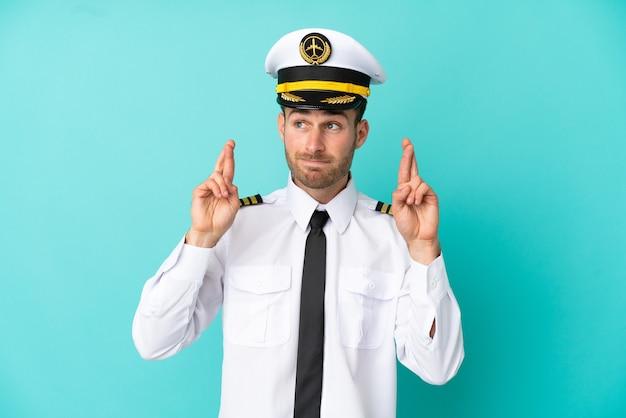 Piloto de avião caucasiano isolado em fundo azul com os dedos se cruzando