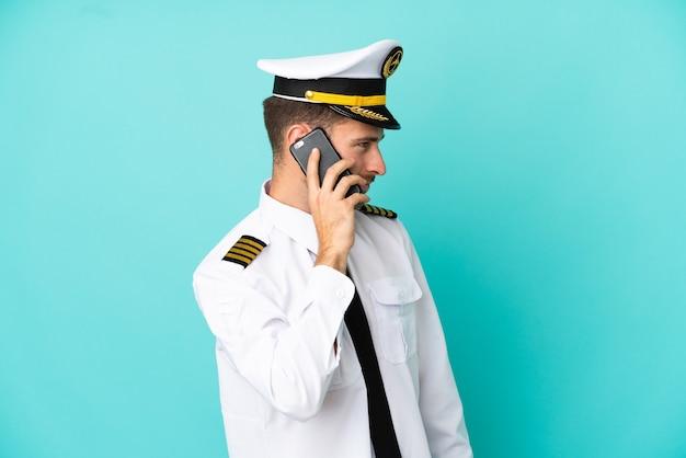 Piloto de avião caucasiano isolado em fundo azul, conversando com alguém ao telefone celular