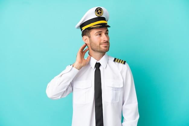 Piloto de avião caucasiano isolado em fundo azul pensando em uma ideia